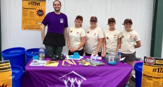 David Mayer, an AmeriCorps serving at COTS, with members of the Rhino Foods team volunteer at the Lake Monsters game on Aug. 2, 2017.